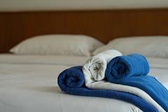 Toalla blanca y azul en cama en dormitorio del hotel fotografía de archivo