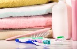Toalla, cepillo para el pelo y cepillos de dientes en tonos en colores pastel Fotografía de archivo