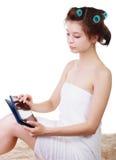 Toalla de baño de la mujer y tableta con que llevan que se sienta en litera de la piel fotos de archivo