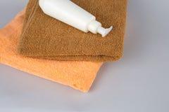 Toalla de Brown y gel de la ducha en un fondo gris crema y toalla de cara en la tabla Disposición de marcado en caliente del BALN imagenes de archivo