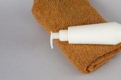 Toalla de Brown y gel de la ducha en un fondo gris crema y toalla de cara en la tabla Disposición de marcado en caliente del BALN imagen de archivo