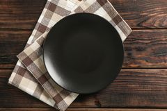Toalla de cocina con la placa en fondo de madera imagen de archivo