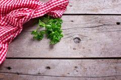 Toalla de cocina roja y blanca y hojas verdes del perejil en rústico foto de archivo