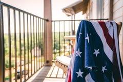 Toalla de la bandera americana en una silla de cubierta sobre la mirada de un lago fotografía de archivo