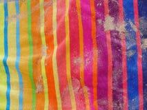 Toalla de playa colorida con la arena Fotografía de archivo