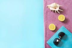 Toalla de playa, gafas de sol y accesorios del verano en fondo azul concepto del recorrido Mofa en blanco para arriba para hacer  Fotos de archivo
