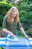 Toalla de té de la mujer que plancha holandesa joven al aire libre Imagen de archivo