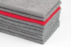 Toalla de Terry roja brillante en la pila otras grises Fondo blanco contraste conceptual del color imagen de archivo