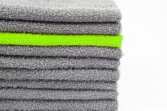 Toalla de Terry verde clara en la pila otras grises Fondo blanco contraste conceptual del color imágenes de archivo libres de regalías