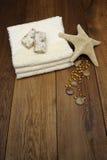 Toalla del algodón, estrella de mar, productos del balneario en la madera s Foto de archivo