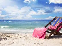 Toalla en sillas de playa en la playa tropical hermosa Imagen de archivo libre de regalías