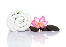Toalla, gladiola y guijarros para el masaje Foto de archivo libre de regalías