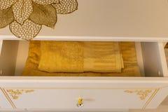 Toalla hermosa amarilla en un pecho de cajones con los partes movibles del oro foto de archivo