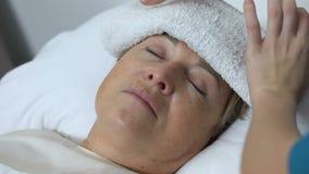 Toalla mojada que pone voluntaria en la frente mayor de la mujer, tratamiento del dolor de cabeza, cuidado metrajes