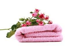 toalla rosada y pequeñas rosas Imagen de archivo libre de regalías