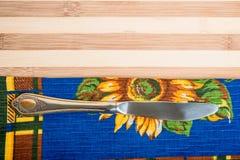 Toalla y cuchillo de cocina en el tablero de madera Fotos de archivo libres de regalías