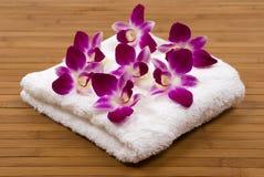Toalla y orquídeas Imagen de archivo libre de regalías