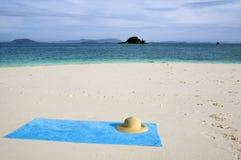 Toalla y sombrero en la playa Fotografía de archivo libre de regalías