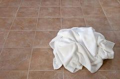 Toallas blancas arrugadas en suelo de cerámica Imagenes de archivo