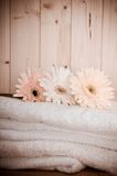 Toallas de baño de la vendimia con las flores en el balneario de madera Foto de archivo libre de regalías