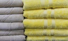 Toallas de Terry dobladas beige y amarillas en el contador de la tienda Fondo de toallas fotos de archivo
