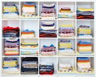 Toallas, hojas de cama y ropa en estante imágenes de archivo libres de regalías