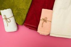Toallas multicoloras en un fondo rosado foto de archivo