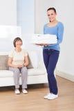 Toallas que llevan del vigilante con la mujer mayor que se sienta en el sofá Fotos de archivo libres de regalías