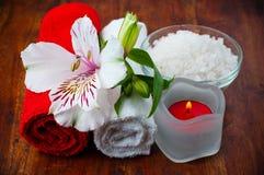 Toallas rojas y blancas, sal aromática y flor Imágenes de archivo libres de regalías