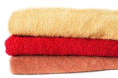 Toallas tres amarillas, rojo, marrón en un fondo blanco imagen de archivo libre de regalías