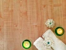 Toallas, velas ardientes, jabón hecho a mano de la flor en la tabla de madera fotos de archivo libres de regalías