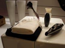 Toallas y accesorios del cuarto de baño en una mesita de noche imagen de archivo