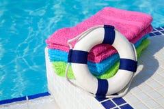 Toallas y boya de vida cerca de la piscina de la nadada Fotos de archivo libres de regalías
