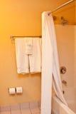 Toallas y ducha en cuarto de baño Imagenes de archivo