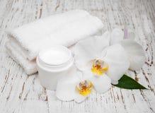 Toallas y orquídeas blancas de la crema del esencial del balneario imagenes de archivo