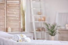 Toallas y velas en la tabla del masaje en salón moderno del balneario Lugar para la relajación fotografía de archivo