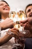 Toast. Close-up of human hands cheering up with flutes of golden champagne Royalty Free Stock Image