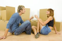 Toast!. Young couple sitting on the floor in flat. They're looking happy. Celebrating removal with champagne and having toast. Side view, whole body Stock Photos