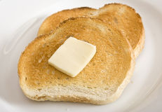 Toast. Two sllices of toast and a slice of butter on a white plate Royalty Free Stock Image