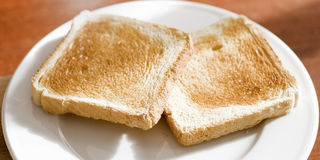 Toast. Two whole grain toast on a white plate Stock Photos