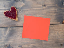 Toast as a heart shape with a red piece of paper Royalty Free Stock Photo