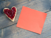 Toast as a heart shape with a red piece of paper Royalty Free Stock Photos
