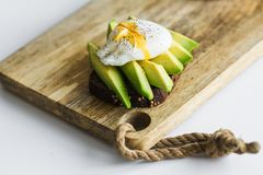 Toast, avacado sandwich and poached egg on a wooden chopping Board. royalty free stock photos