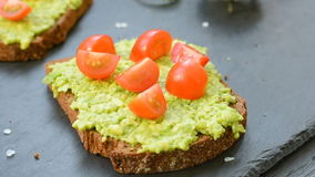 Toast with avocado, cherry tomatoes and spices stock footage