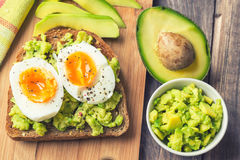 Toast with avocado and egg. On rustic wooden background stock photos
