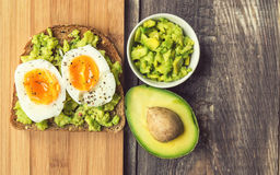 Toast with avocado and egg. On rustic wooden background Royalty Free Stock Photo