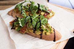 Toast with avocado and sauce on the table royalty free stock image