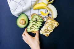 Toast with avocado, sesame and peanut butter on whole grain bread and toast with banana and flaxseed on whole wheat bread stock photo