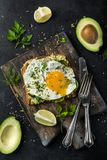 Toast with avocado, spinach and fried egg on wooden cutting boar Stock Photos