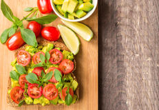Toast with avocado, tomatoes and basil. On rustic wooden background Royalty Free Stock Image